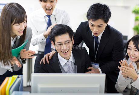 パソコンを見て喜ぶビジネス男女の写真素材 [FYI02967631]