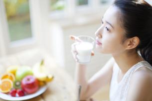 牛乳の入ったコップを持った女性の写真素材 [FYI02967639]