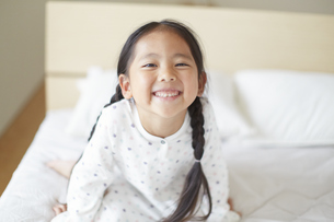 ベットの上で笑うパジャマ姿の女の子の写真素材 [FYI02967642]