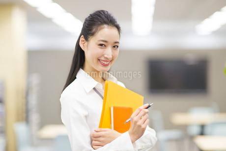 オフィスでファイルを手に微笑むビジネス女性の写真素材 [FYI02967643]