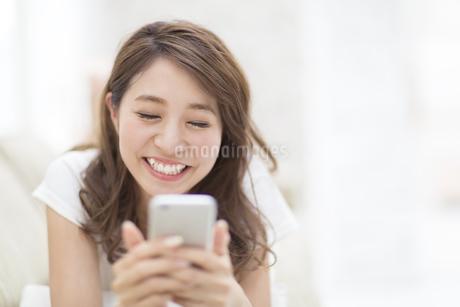 ソファの上でスマートフォンを見る女性の写真素材 [FYI02967645]