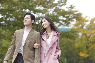公園で腕組みして歩くカップルの写真素材 [FYI02967650]