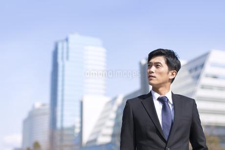ビルを背景に上を見るビジネス男性の写真素材 [FYI02967654]