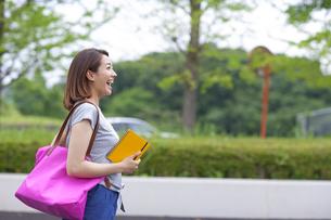 立ち止まって微笑む女子学生の写真素材 [FYI02967656]
