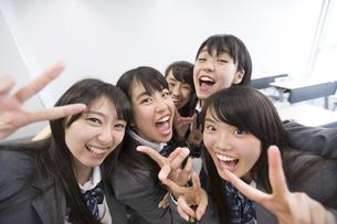 教室でピースをする女子高校生たちの写真素材 [FYI02967662]