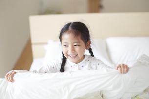 ベットの上で笑うパジャマ姿の女の子の写真素材 [FYI02967663]