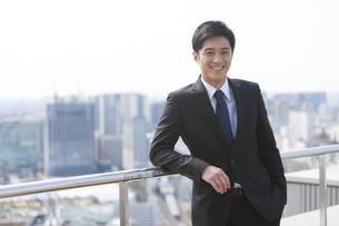 柵に肘をかけて微笑むビジネス男性の写真素材 [FYI02967666]