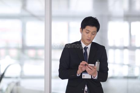 スマートフォンを触るビジネス男性の写真素材 [FYI02967667]