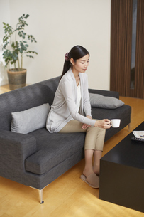 ソファーでカップを手にする女性の写真素材 [FYI02967668]