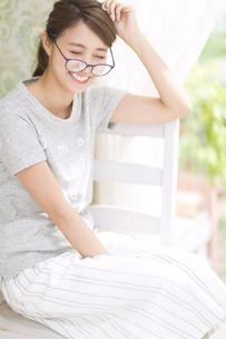 カーテンの傍で椅子に座って眼鏡を掛け笑う女性の写真素材 [FYI02967669]