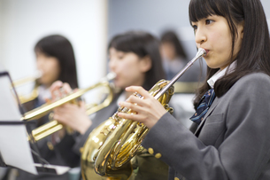 音楽室で吹奏楽の練習をする女子学生たちの写真素材 [FYI02967670]