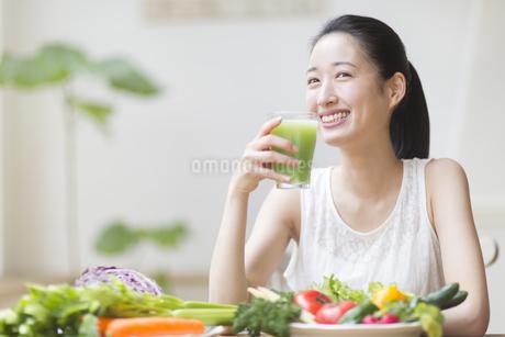 スムージーを手に微笑む女性の写真素材 [FYI02967673]