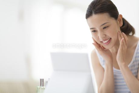 鏡の前でスキンケアをする女性の写真素材 [FYI02967677]