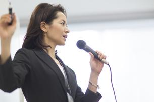 マイクを手に講義するビジネス女性の写真素材 [FYI02967678]