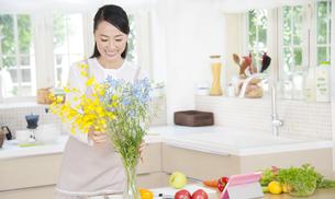 花瓶に花を飾る奥さんの写真素材 [FYI02967679]
