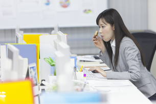お菓子を食べながらパソコンを見るビジネス女性の写真素材 [FYI02967683]