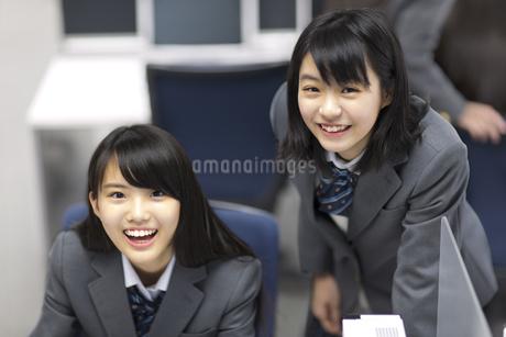 パソコン教室でモニターの前で顔を上げ微笑む2人の女子高校生の写真素材 [FYI02967688]