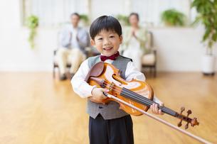 祖父母の前でバイオリンを持つ男の子の写真素材 [FYI02967694]