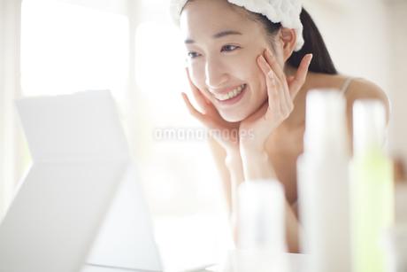 鏡の前でスキンケアをする微笑む女性の写真素材 [FYI02967695]