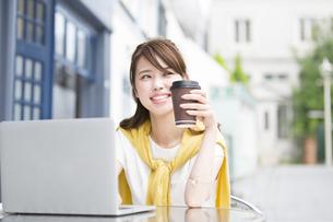 街中でノートPCを操作する女性の写真素材 [FYI02967698]