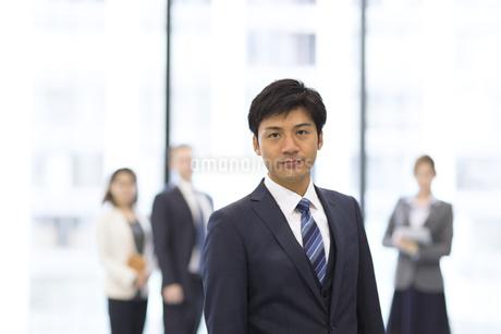 オフィスビルのロビーで立つビジネス男性のポートレートの写真素材 [FYI02967699]