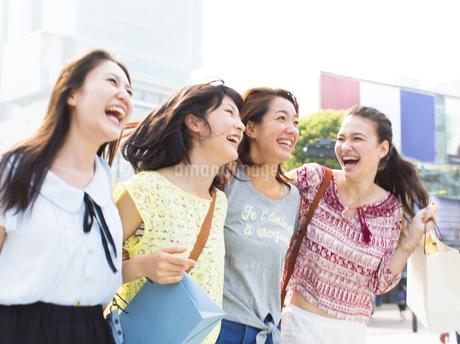 街で肩を合わせて歩く4人の女性の写真素材 [FYI02967705]