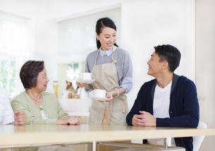 家族の座るテーブルにカップを運ぶ奥さんの写真素材 [FYI02967707]