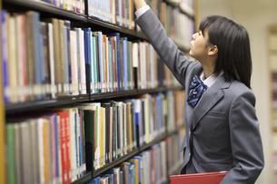 図書室で本を探す女子高校生の写真素材 [FYI02967709]