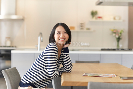 ダイニングテーブルでほほづえをついて微笑む女性の写真素材 [FYI02967710]