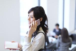 スマートフォンで通話するビジネス女性の写真素材 [FYI02967711]