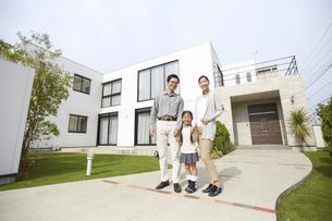 家の前に立つ3人家族の写真素材 [FYI02967717]