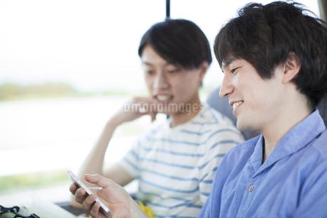 バスの中でスマートフォンを見る2人の男性の写真素材 [FYI02967718]