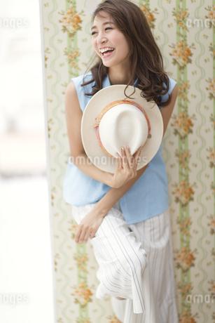 壁に寄り掛かって帽子を持って笑う女性の写真素材 [FYI02967721]