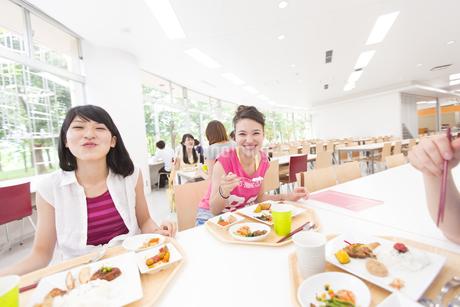 学食で食べながら笑う学生たちの写真素材 [FYI02967722]