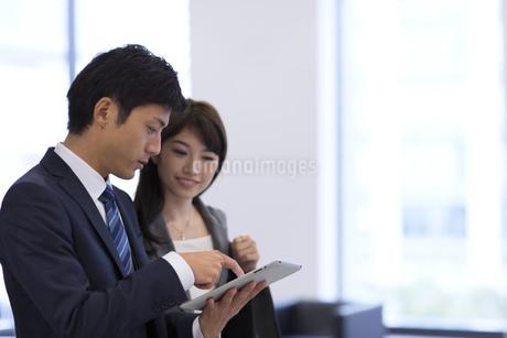 オフィスでタブレットPCを見るビジネス男女の写真素材 [FYI02967724]