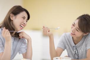 食事をしながら笑い合う2人の女性の写真素材 [FYI02967740]