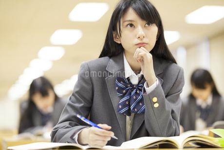 図書室で勉強中に顔を上げる女子高校生の写真素材 [FYI02967747]