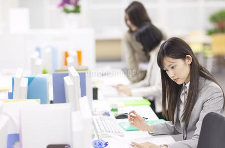 デスクで資料を見るビジネス女性の写真素材 [FYI02967748]
