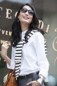 ウィンドウの前でサングラスをかけて微笑む女性の写真素材 [FYI02967749]