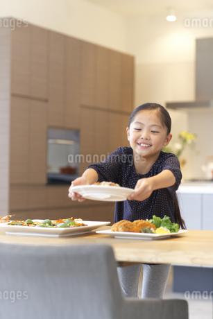 テーブルに食事を用意する女の子の写真素材 [FYI02967756]