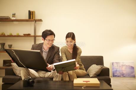 額装を手にソファーで語らう夫婦の写真素材 [FYI02967758]