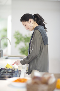キッチンで料理の準備をする女性の横顔の写真素材 [FYI02967763]