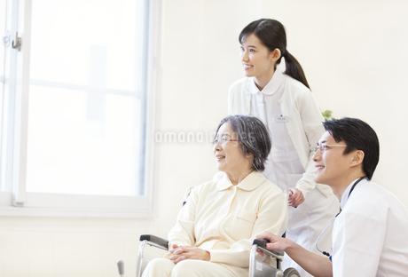 車椅子の患者に添う男性医師と女性看護師の写真素材 [FYI02967764]
