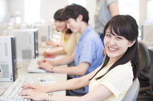 パソコンを前に微笑む女子学生のポートレートの写真素材 [FYI02967765]
