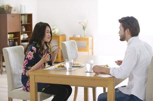 ダイニングテーブルで食事を楽しむ男性と女性の写真素材 [FYI02967766]
