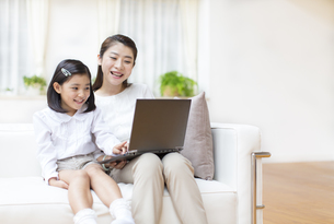 ノートPCを見ながら笑う母と娘の写真素材 [FYI02967767]