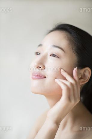 頬に片手を添えて上を見上げる女性の写真素材 [FYI02967769]
