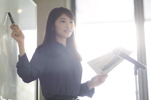 資料を持って演台で話すビジネス女性の写真素材 [FYI02967770]