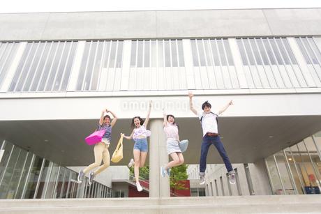 建物の前でジャンプする学生たちの写真素材 [FYI02967772]