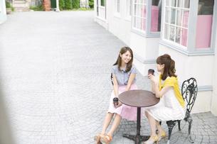 街中でカップを持って会話を楽しむ2人の女性の写真素材 [FYI02967773]